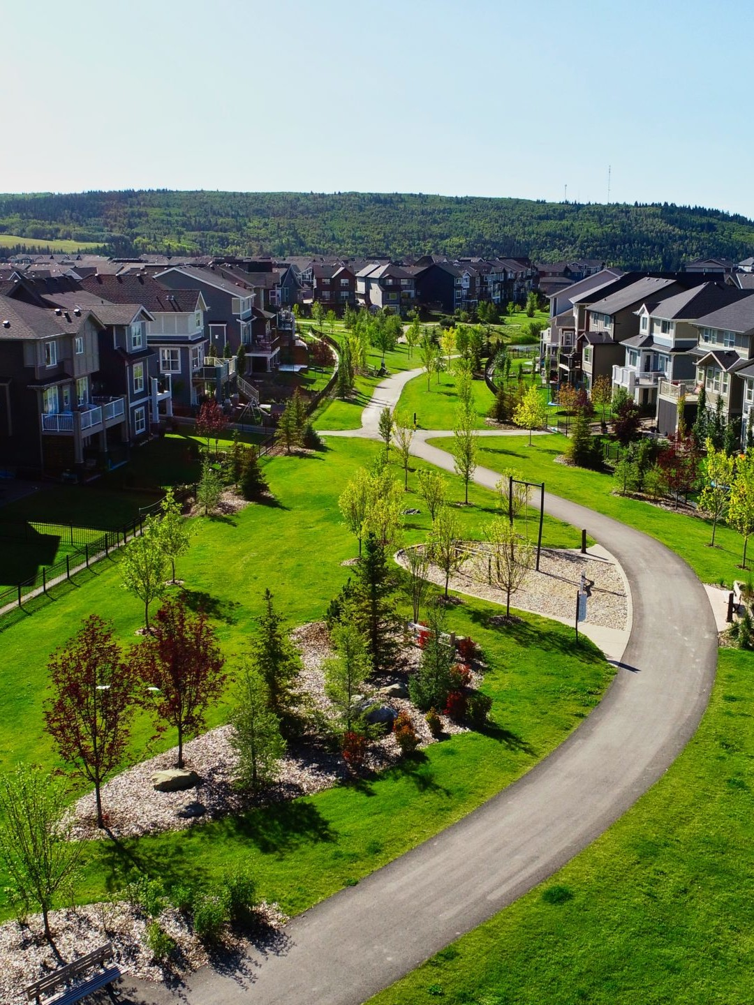 A multi-use path winds through the community of Sunset Ridge. The path is lushly landscaped, dotted with picnic tables and benches, and features bollard lighting for evening safety.